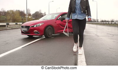 Car accident on the road, the girl puts a warning sign near the car.