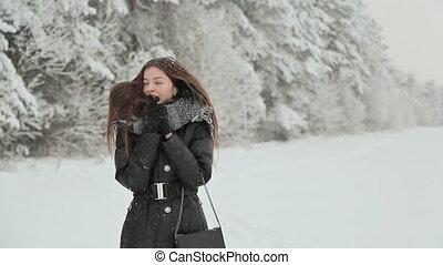 A young girl in winter clothes with long hair enjoys a walk along the snow-covered forest under the falling snow.