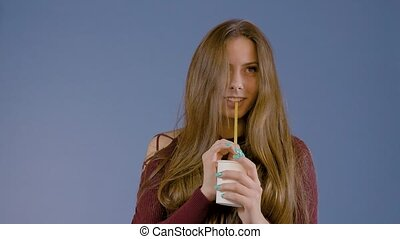 A young girl is holding a paper cup with a drink. In the studio on a blue background. Photography for advertising.