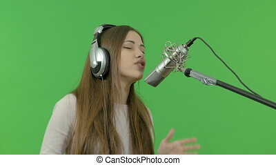 A young girl is singing into a studio microphone. close-up. On a green background.