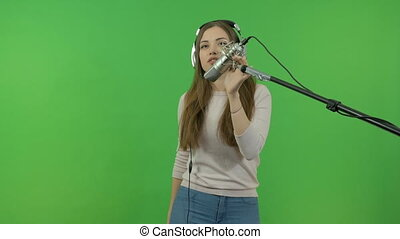 A young girl is singing into a studio microphone. On a green background.