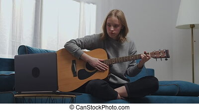 A young girl is sitting on the sofa in the lotus position in the living room. A woman learns to play the guitar alone. She is watching her first online lesson on her laptop.