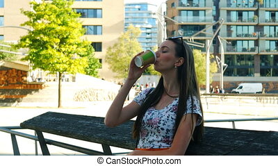 A young girl is waiting for someone in the city and drinking a coffee to go