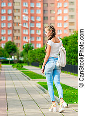 a young girl is walking around the city with a backpack, a back view