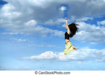 A young girl jumping in front of blue sky and clouds