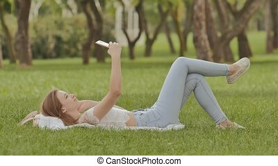 A young girl lies on her back in the green grass with a smartphone in her hands. Fun posing on camera phone. Recreation. Summer day, sunny weather.