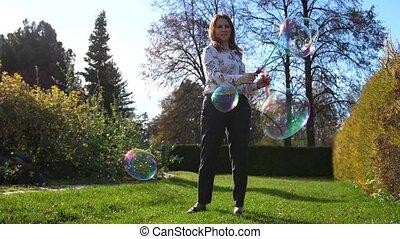 A young girl makes big soap balls. Outdoor entertainment -...
