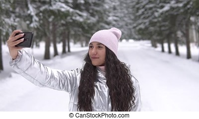 A young girl makes selfie using a smartphone while standing in a winter forest. slow motion HD