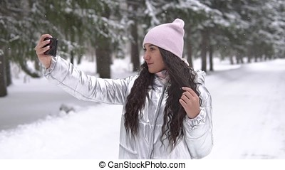 A young girl makes selfie using a smartphone while standing in a winter forest. slow motion