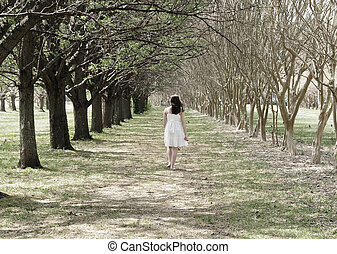 A young girl peacefully walking between the rows of trees on a Spring morning, Tranquility defined.