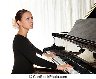 A young girl playing the piano