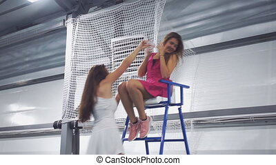 A young girl pours water on his girlfriend tennis player and...