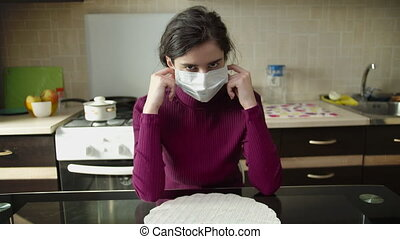 A young girl removes a medical mask while sitting at home, in the background of the kitchen