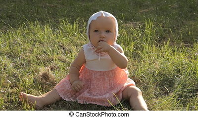 A young girl rocking from side to side on the grass with half a hand in her mouth.