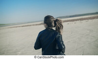 A young girl runs through the open countryside and turns...