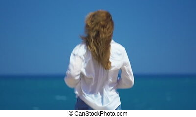 A young girl runs up to the cliff above the beautiful sea....