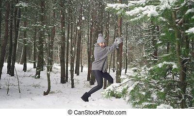 A young girl shakes a tree in the forest and snow falls on her. Slow mo