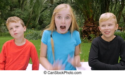 A young girl shows excitement and surprise while two boys imitates her