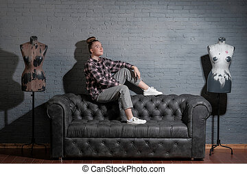 A young girl sits on a leather sofa against a gray brick wall.