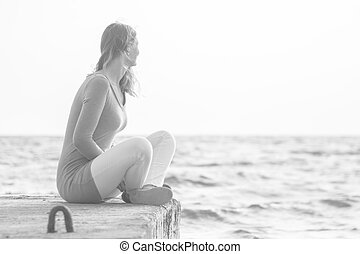 A young girl sits on a pier and looks out into the distance at sea