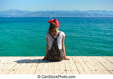 A young girl sits on a wooden pier and looking at the sea.