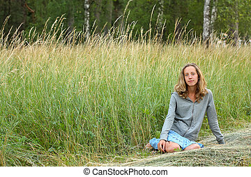 A young girl sitting in the grass