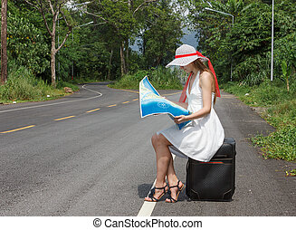 a young girl sitting on a suitcase with a map
