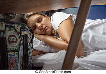 A young girl sleeps on the bottom bunk in a train