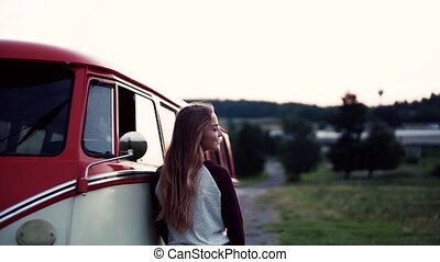 A young girl standing y a car on a roadtrip through...