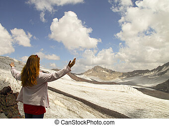 A young girl stands on the edge of a cliff and looking at the sk