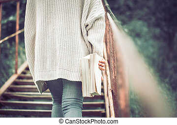 girl stands on the steps of a staircase with a book
