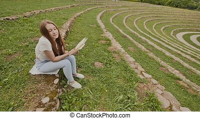 A young girl student is reading a book sitting on the grass amidst a large stadium. Preparation for study.