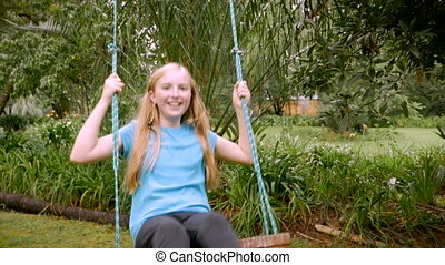 A young girl swings directly in front of the camera in...