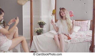 A young girl takes pictures of her girlfriend with a candy in the bedroom