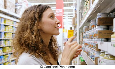 A young girl takes the baby food in the store, 4k.