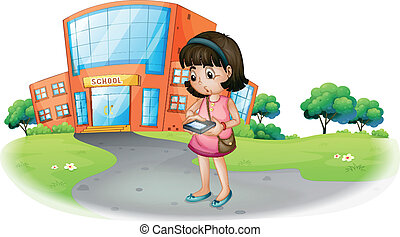 A young girl texting in front of a school building