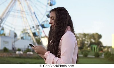 A young girl walks by the ferris wheel and uses a smartphone. 4K.