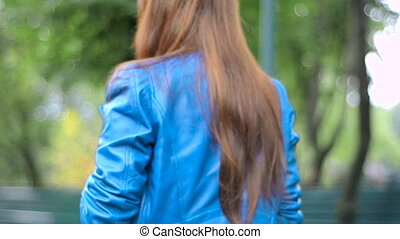girl walks down the street in blue leather jacket
