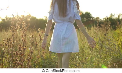 a young girl walks through a field at sunset, slow motion, back view