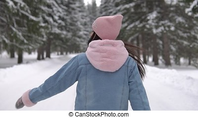 A young girl walks through a winter forest with good nutrition and swirls around herself. slow motion