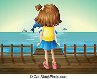 A young girl watching the dolphins