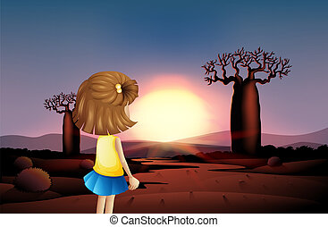 A young girl watching the sunset at the desert