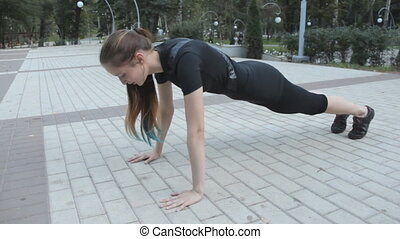 A young girl wearing athletic apparel doing pushups in a park with her hands rested on the ground. On a stone tiled ground.