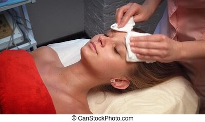 young girl wipe face and neck with a cotton napkin