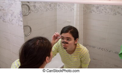 A young girl with a black cosmetic mask on her face looks at herself in the mirror