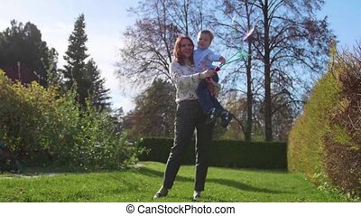 A young girl with a child playing in the Park on the lawn....