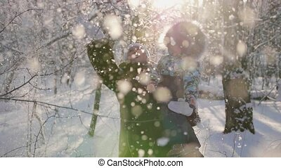 A young girl with a child playing in winter Park. Snowfall....