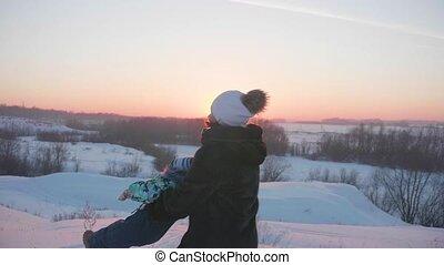 A young girl with a child playing in winter Park.Walks in the fresh air. Sunset