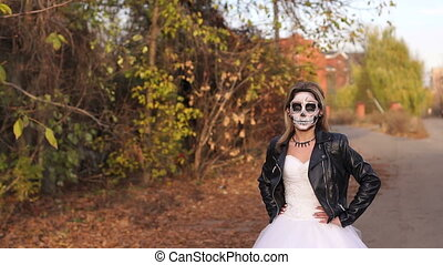 A young girl with a creepy make-up in the form of a skull on a empty road.