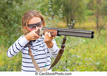 A young girl with a gun for trap shooting and shooting...